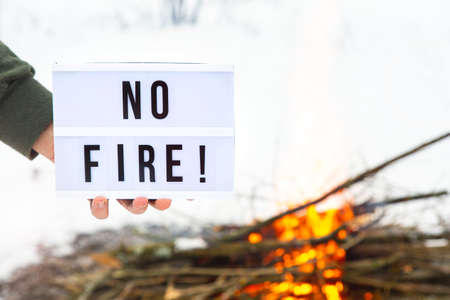 A sign with the text no fire in a mans hand over a flaming bonfire on a white background.