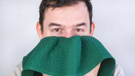 Close-up of a Caucasian man wiping his face with a green towel.