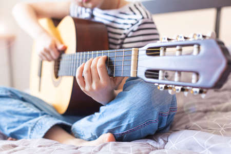 The child plays an acoustic guitar. Learning to play a musical instrument online