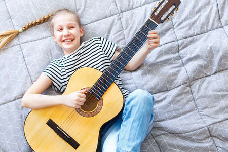 Happy girl playing acoustic guitar at home, lying on the bed, top view.