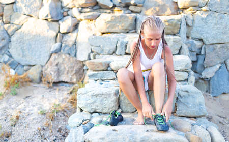 Sitting on the stone steps, a Caucasian teenage girl with pigtails puts on climbing shoes. The child prepares for outdoor rock climbing. Healthy, active lifestyle. Alpinism, mountaineering.