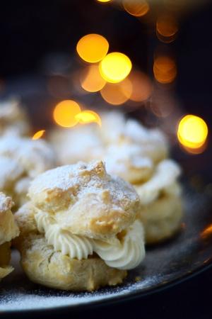 Profiteroles with powdered sugar on a dark background Stock Photo