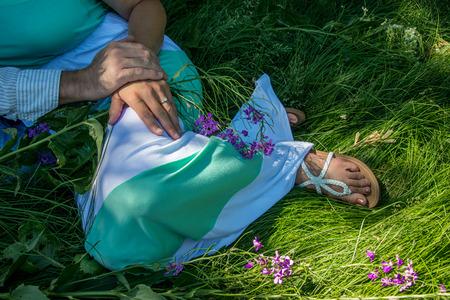 amongst: A man and woman rest amongst the summer grass.