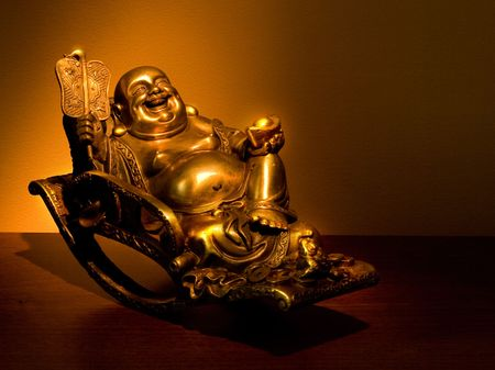 Hotei chinese god of wealth, prosperity and happiness seating in the rocking-chair 版權商用圖片