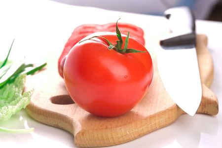 Red ripe fresh tomato on cutting board with sliced red sweet pepper, green onion and bok choy leafs photo