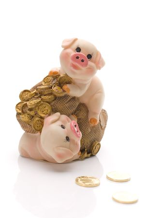Two funny pigs with pouch of gold coins over white. Clay piggy. photo