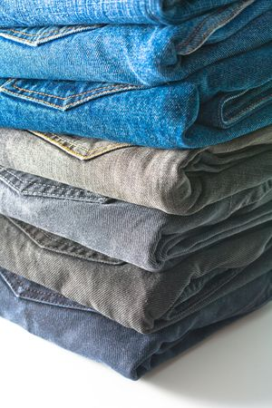 Stack of folded jeans over white background photo