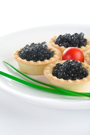 Tartlet with black caviar on a white platter, decorated with cherry tomatoes and green onions