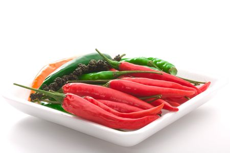 Bowl of ripe colorfull chili pepper over white background