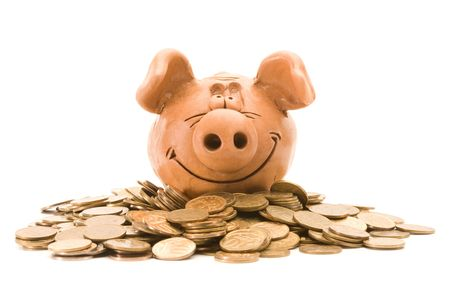 Pig bank seat on a heap of coins isolated over white background