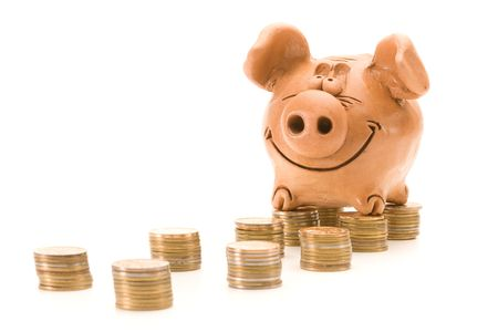 Pig bank seat on a stack of coins isolated over white background