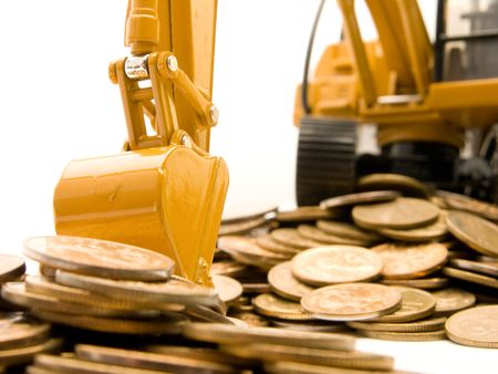 Yellow excavator digging a heap of coins isolated over white background