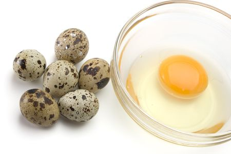 Dish of liquid egg and quail eggs over white background