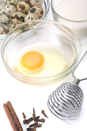 Dish of liquid egg, sugar, whisk and quail eggs over white background