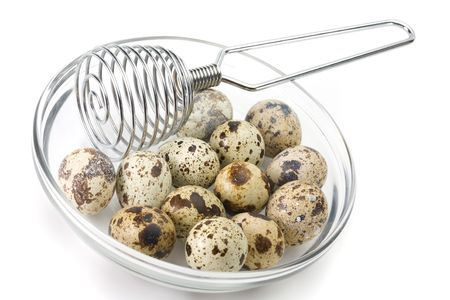 Dish of quail eggs and whisk over white background