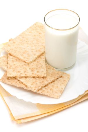 Glass of milk and dish of crackers over table-napkin isolated on white background 版權商用圖片