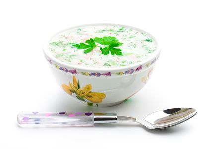 Bowl of cold soup with chopped vegetables, potherbs, meat and kvass over white background Stock fotó