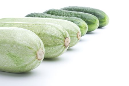 Raw ripe cucumbers and squashs on a white background