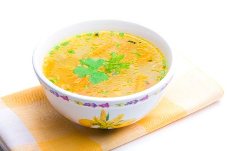 Bowl of chicken soup over yellow napkin on a white background