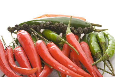 pile of ripe chilli peppers on a white background