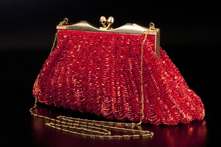 Red evening bag over black background