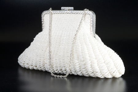 White evening bag over black background