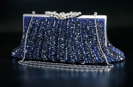Blue evening bag over black background