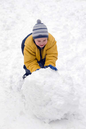 rolling: The boy rolls snow whom in winter day