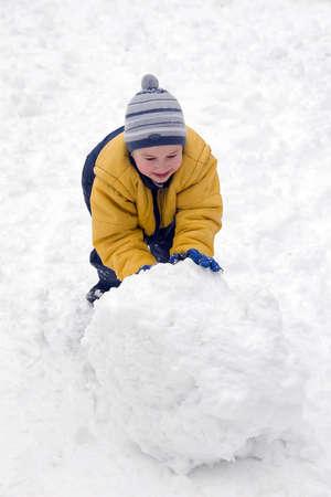 The boy rolls snow whom in winter day
