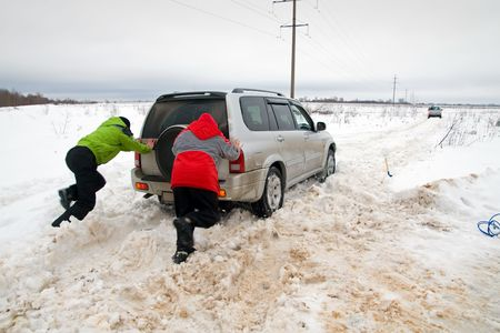 Two men pushing a car that stuck in the snow