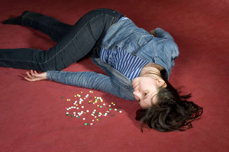 human body substance: Woman suicide with pills. Simulated, studio shot.