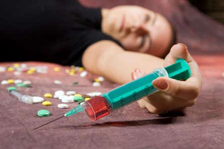 Drug addict with syringe. Simulated, studio shot. photo