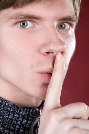 shushing: Young man shushing with finger to mouth.