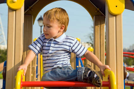 The boy climb on the equipment of a playground Stock Photo - 3575073