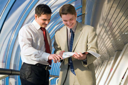 Two young businessmen discuss results of work photo