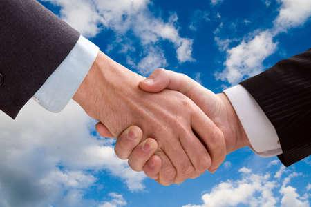 mani che si stringono: Due uomini d'affari stringe la mano su uno sfondo di cielo