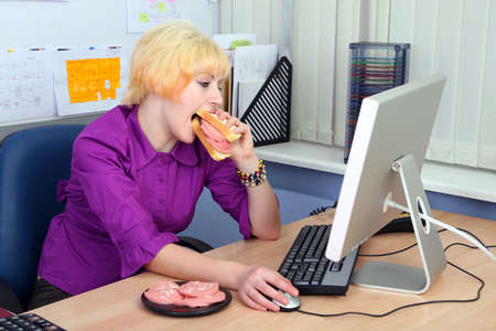 The young woman has breakfast a sandwich with sausage on work photo