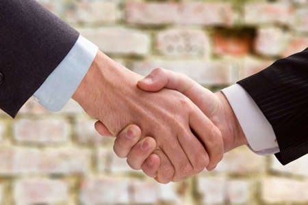 Two business men shaking hands on a background of a brick wall