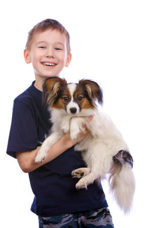 Boy bearing a puppy in his arms.  photo