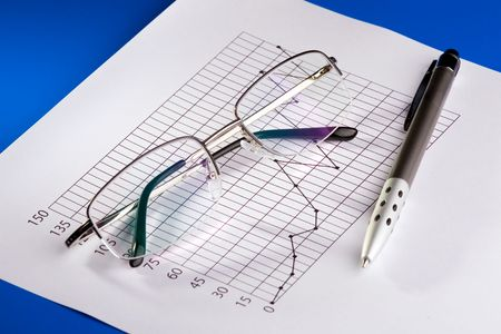 A pen and glasses composed over a business chart of earnings growth. photo