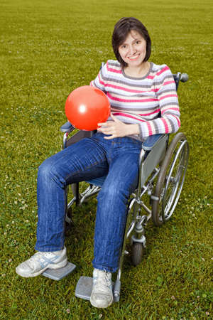 Woman in wheelchair with a red ball in hands