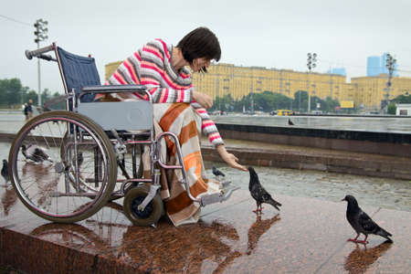 Woman in wheelchair feeds pigeons in street cities photo