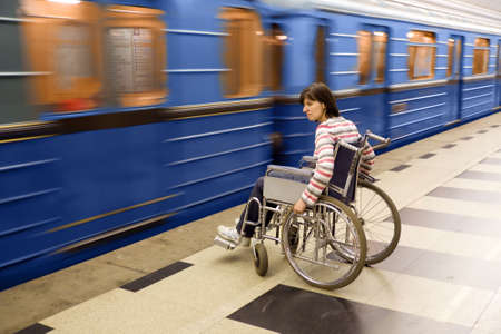Woman in wheelchair near to passing train of subway
