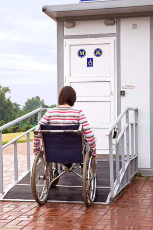 on ramp: woman in wheelchair drives to a toilet for invalids