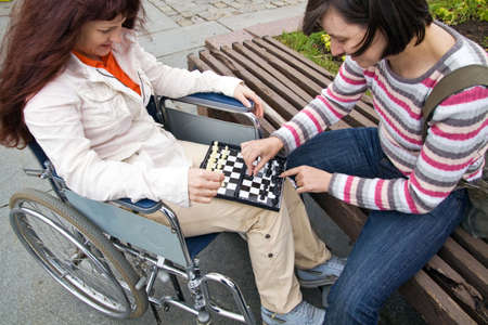 woman in wheelchair plays with girlfriend in a chess