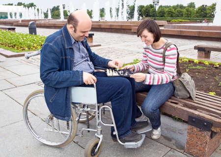 discapacitados: la mujer y el hombre en una silla de ruedas jugar un juego de ajedrez Foto de archivo