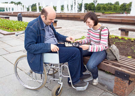 behindert: Mann und Frau auf einem Rollstuhl spielen Schach Lizenzfreie Bilder