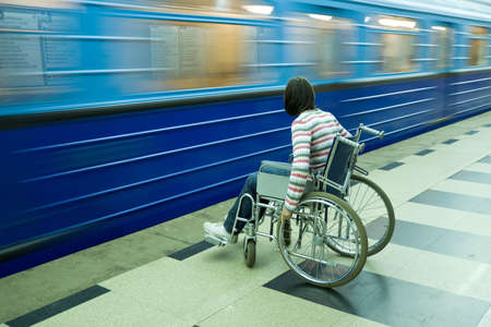 Woman in wheelchair near to passing train of subway photo