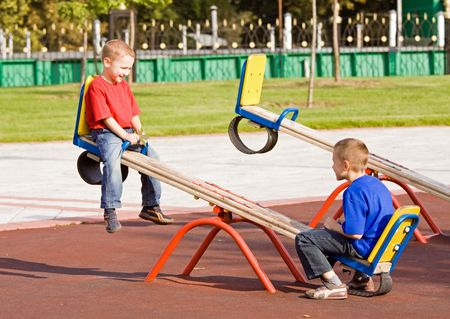 Jongens spelen op een wip op een speelplaats in een zonnige dag