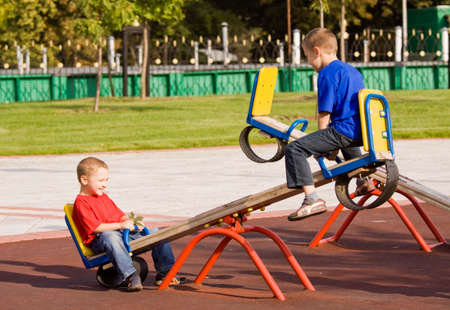 Boys playing on a seesaw on a playground in a sunny day